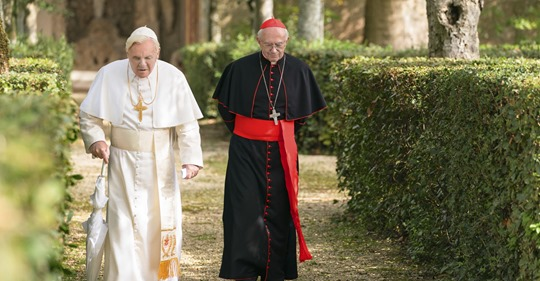 Anthony Hopkins and Jonathon Pryce walking outside in scene from The Two Popes directed by Fernando Merielles of Saville Productions